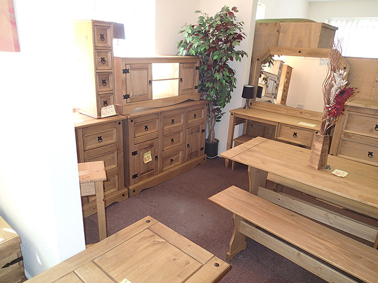Wooden furniture on display including a desk, draws, and mirror.